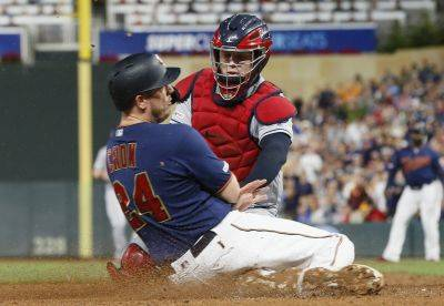 Minnesota's C.J. Cron is tagged by Cleveland catcher Roberto Perez during Saturday night's game in Minneapolis. (AP photo)