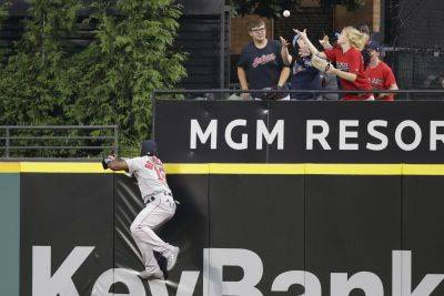 Boston's Jackie Bradley Jr. jumps on the wall but can't get to the Indians' Carlos Santana's solo home run during Tuesday night's game in Cleveland. (AP photo)