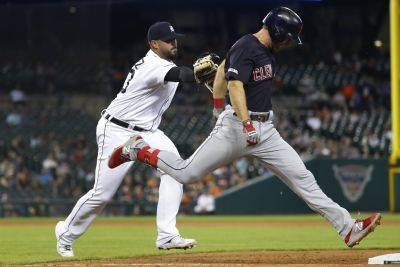 Cleveland's Mike Freeman beats the tag attempt of Tigers relief pitcher Nick Ramirez covering first base for a single in the seventh inning of Tuesday night'sl game in Detroit. (AP photo)