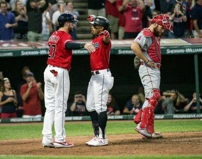 The Indians' Kevin Plawecki (27) greets Francisco Lindor after Lindor's three-run home run off Los Angeles Angels relief pitcher Justin Anderson as  catcher Kevan Smith, right, looks away during Saturday night's game in Cleveland. (AP photo)