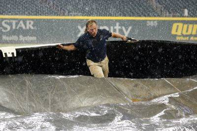 A member of the Braves grounds crew works to cover the field during a rain shower Thursday night in Atlanta. (AP photo)
