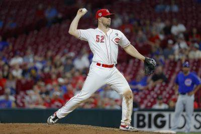 The Reds' Kyle Farmer was called upon to pitch in the ninth inning after playing second base during Thursday night's game against the Chicago Cubs in Cincinnati. (AP photo)