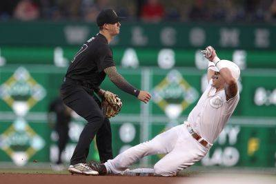 Pirates shortstop Kevin Newman forces out Cincinnati's Derek Dietrich at second and throws on to first to complete the double play on Phillip Ervin during Saturday night's game in Pittsburgh. (AP photo)