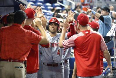 Cincinnati Reds' Jose Iglesias (4) is congratulated by teammates after he and Eugenio Suarez scored on a single by Curt Casali during the fifth inning of Tuesday night's game against the Marlins in Miami. The Reds won 8-5. (AP photo)