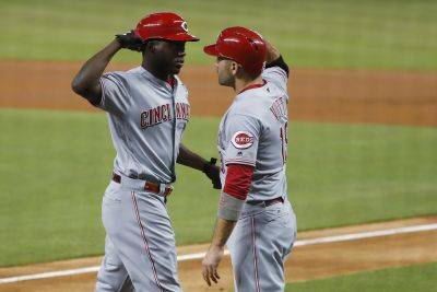 Cincinnati Reds' Aristides Aquino, left, is congratulated by Joey Votto hitting a home run during Thursday night's game against the Marlins in Miami. (AP photo)
