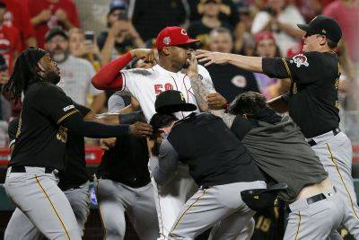 The Reds' Amir Garrett is held back by a number of Pittsburgh Pirates players during a brawl in the ninth inning of Tuesday night's game in Cincinnati. (AP photo)