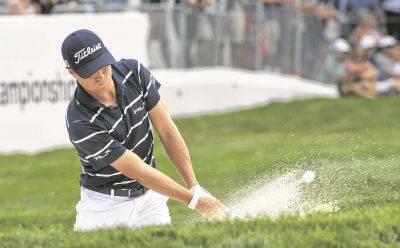 Justin Thomas hits from the bunker on the 18th green during Thursday's first round of the BMW Championship at Medinah Country Club in Medinah, Ill.