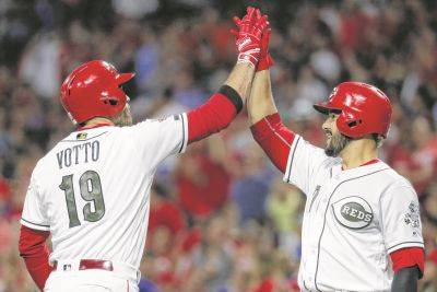 The Reds' Joey Votto celebrates with Eugenio Suarez after hitting a solo home run during Friday night's game against the Chicago Cubs in Cincinnati.