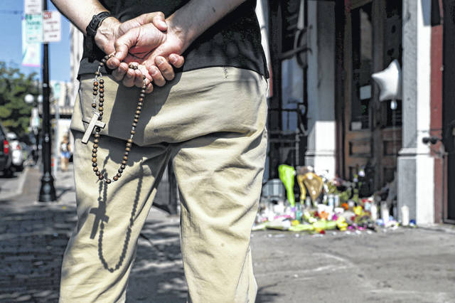 A mourner prays his rosary beads beside a memorial outside Ned Peppers bar. (AP Photo/John Minchillo)