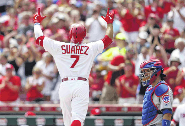 Cincinnati Reds' Eugenio Suarez (7) reacts as he crosses the plate with a solo home run off Chicago Cubs starting pitcher Jon Lester during the fifth inning of a baseball game, Sunday, Aug. 11, 2019, in Cincinnati. Cubs catcher Victor Caratini, right, looks on, (AP Photo/Gary Landers)