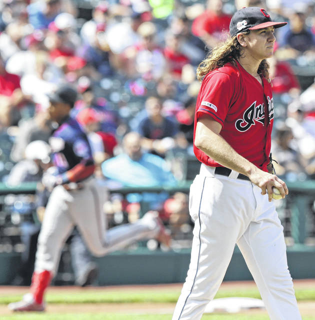 Indians pitcher Mike Clevinger, right, waits as Minnesota's Jorge Polanco runs the bases after hitting a two-run home run during the first game of a Saturday doubleheader in Cleveland.