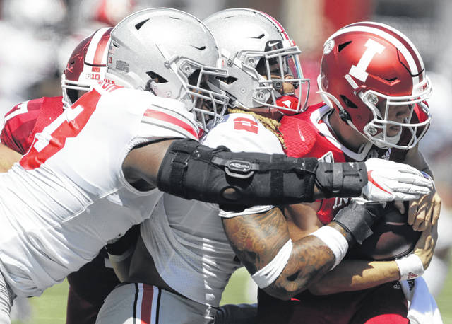 Ohio State's defensive end Chase Young, center, and Davon Hamilton sack Indiana quarterback Peyton Ramsey during Saturday's game in Bloomington, Ind.