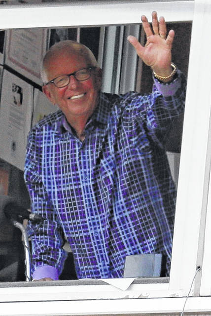 Reds announcer Marty Brennaman waves from his booth during Thursday's game against Milwaukee in Cincinnati.