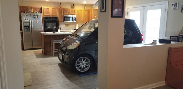 "In this Sept. 3, 2019 photo made available by Jessica Eldridge shows her husband's Smart car parked in their kitchen in Jacksonville, Fla. Patrick Eldridge parked his Smart car in his kitchen to protect it from Hurricane Dorian. In a Facebook post, Jessica Eldridge said her husband was ""afraid his car might blow away"" so he parked it in their Jacksonville home's kitchen. (Jessica Eldridge via AP)"
