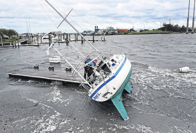 Beaufort Police Officer Curtis Resor, left, and Sgt. Micheal Stepehens check a sailboat for occupants in Beaufort, N.C., after Hurricane Dorian passed the North Carolina coast on Friday. Dorian howled over North Carolina's Outer Banks as a much weaker but still dangerous version of the storm that wreaked havoc in the Bahamas. It flooded homes in the low-lying ribbon of islands and throwing a scare into year-round residents who tried to tough it out.