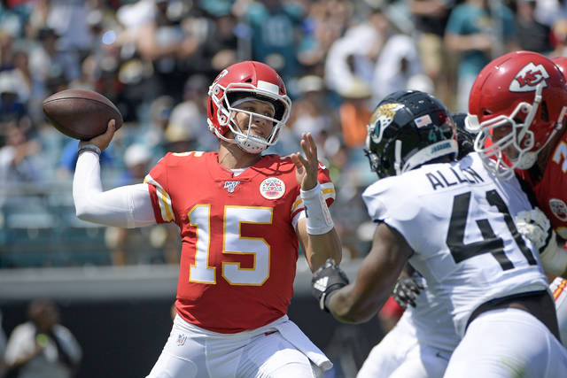 Kansas City Chiefs quarterback Patrick Mahomes (15) throws a pass as he is pressured by Jacksonville Jaguars defensive end Josh Allen during the first half of an NFL football game, Sunday in Jacksonville, Fla.