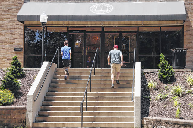 Visitors walk the stairs to Alexander Hall on the campus of Geneva College in Beaver Falls, Pa., in August. Whether it's money for books, living expenses or something else, students starting the new school year may quickly realize their financial aid won't cover all the costs of college.