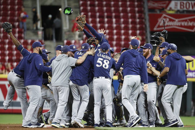 The Milwaukee Brewers celebrate a 9-2 win over the Cincinnati Reds in a baseball game Wednesday, Sept. 25, 2019, in Cincinnati. (AP Photo/John Minchillo)