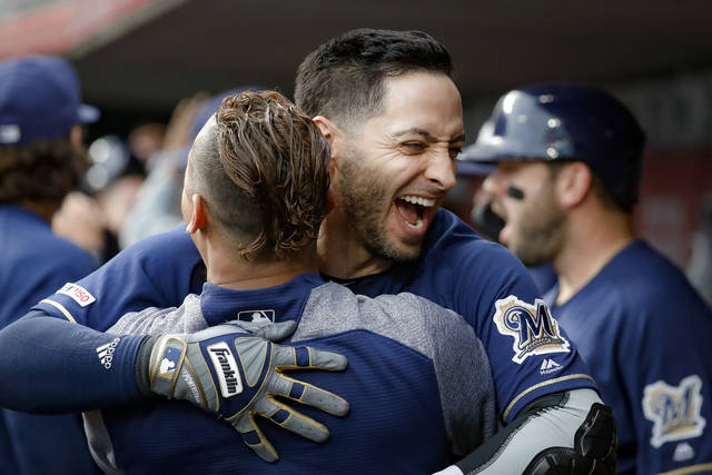 Milwaukee Brewers' Ryan Braun, center, celebrates in the dugout after hitting a grand slam off Cincinnati Reds starting pitcher Tyler Mahle during the first inning of a baseball game Wednesday, Sept. 25, 2019, in Cincinnati. (AP Photo/John Minchillo)