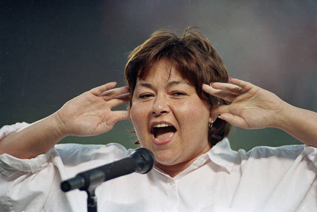 FILE - In this July 25, 1990, file photo, comedienne Roseanne Barr holds her fingers in her ears as she screams the National Anthem between games of the San Diego Padres and the Cincinnati Reds doubleheader in San Diego, Calif. A Delaware school district played a parody version of the national anthem before a volleyball match, surprising spectators with Barr's screeching 1990s rendition. The News Journal of Wilmington reports the Seaford School District apologized Wednesday, Sept. 25, 2019, for the shock at its Tuesday game with Milford High. Superintendent David Perrington says pre-game proceedings will be improved. Officials didn't say how Barr's version, performed before a San Diego Padres game, came to be used. (AP Photo/Joan Fahrenthold, File)