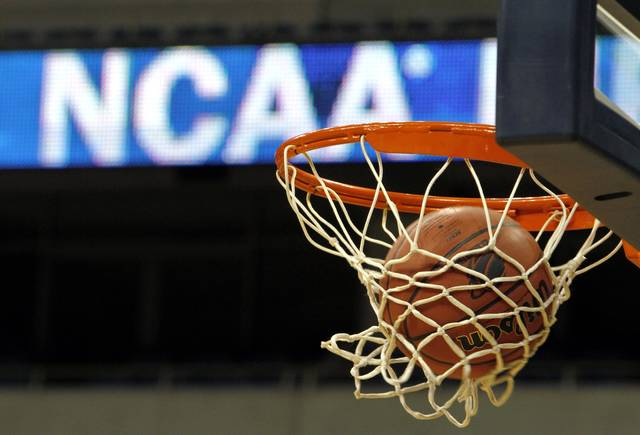 FILE - In this March 20, 2010, file photo, a ball flicks through the net in front of the NCAA logo on the marquis during an NCAA college basketball practice in Pittsburgh. Defying the NCAA, California's governor signed a first-in-the-nation law Monday, Sept. 30, that will let college athletes hire agents and make money from endorsements — a move that could upend amateur sports in the U.S. and trigger a legal challenge. (AP Photo/Keith Srakocic, File)