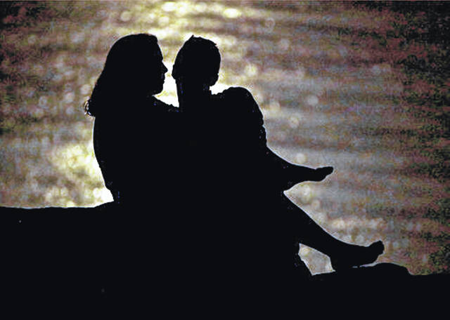 FILE - In this June 27, 2018, file photo a couple is silhouetted against moonlight reflecting off the Missouri River as they watch the full moon rise beyond downtown buildings in Kansas City, Mo. Money won't buy happiness, but it can sure sow discord in a relationship. That's why talking about money with your partner is important. Regular money summits can help you touch base on important financial goals and give you peace of mind about the state of your union and your finances. (AP Photo/Charlie Riedel, File)