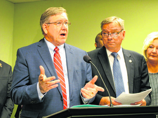 State Reps. Bob Cupp, left, and John Patterson discuss the latest version of their proposal to overhaul Ohio's school funding system at the Statehouse in Columbus, Ohio, on June 26.