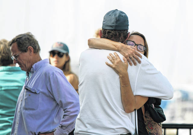 People hug each other as they await news outside of the Truth Aquatics office in Santa Barbara, Calif., on Monday, Sept. 2, 2019. Multiple people are feared dead after a dive boat caught fire before dawn Monday off the Southern California coast, according to the Coast Guard.