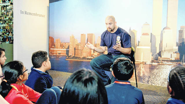 "This image released by HBO shows a New York City Fireman speaking to children in a scene from the documentary ""What Happened on September 11,"" a short film aimed at young people to explain to them what happened on Sept. 11, 2001. The program debuts on Wednesday."