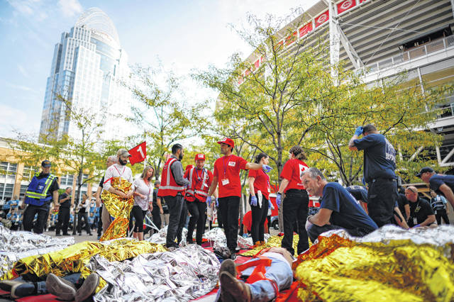 First responders stage a simulated triage outside Great American Ball Park during a mass casualty training exercise, Thursday, Sept. 19, 2019, in Cincinnati. Hundreds of people, some covered in fake blood, are playing victims of a terrorist attack in Cincinnati's riverside entertainment area in training exercise. The morning-long exercise at The Banks area and at Great American Ball Park, where the Cincinnati Reds play, used a scenario of a large truck carrying chemicals crashing into a crowd. Regional emergency management agencies, first responders and hospitals took part in the large-scale exercise .