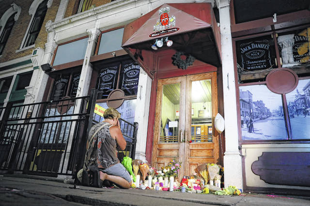 FILE - In this Aug. 4, 2019 file photo, mourners visit a makeshift memorial outside Ned Peppers bar following a vigil at the scene of a mass shooting in Dayton, Ohio. As soon as six Ohio police officers hailed as heroes killed the gunman to end an attack that claimed nine lives in Dayton, police began work to save the wounded. Their at-the-scene aid was the latest example of how police have taken on an increased medical role in mass shootings, among any adjustments in tactics, weapons, equipment and training U.S. law enforcement agencies have made as shootings have mounted.