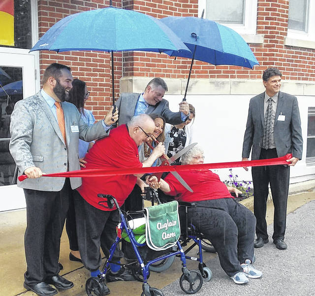 Rainy skies didn't deter residents of the Acres of Wapakoneta from cutting the ribbon Sunday at the former Augtlaize Acres nursing home.