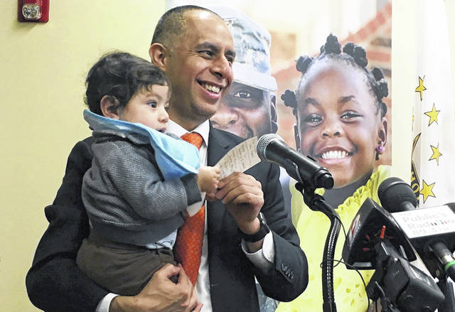 Mayor Jorge Elorza holds his son Omar during a news conference in Providence, R.I. Elorza's decision to frequently take his son to work with him has brought praise from some who say he's a role model, but also raised questions about whether he has taken it too far. (Steve Klamkin/WPRO News via AP)