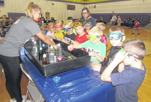 Olivia Rump, Ottawa-Glandorf High School senior, helps Glandorf elementary second grade students make slime during a COSI on Wheels Day Tuesday.
