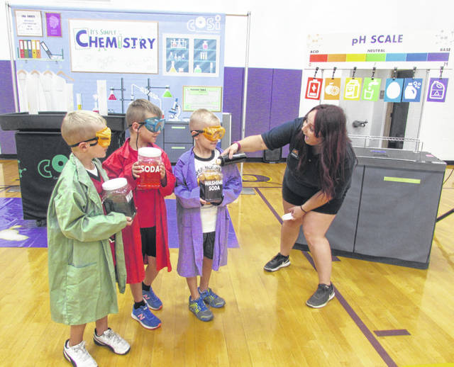 Jessica Takos, COSI on Wheels manager of Camp-in overnight program, works with Glandforf Elementary school first graders from left, Connor Ellerbrock, Landry Wrasman and Mason Verhoff on a pH experiment.