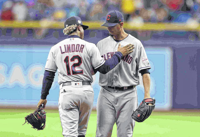 Cleveland Indians shortstop Francisco Lindor (12) pats Indians pitcher Carlos Carrasco on the chest after he warmed up during the seventh inning of a baseball game against the Tampa Bay Rays Sunday, Sept. 1, 2019, in St. Petersburg, Fla. Carrasco is making his first appearance since May, when he was diagnosed with leukemia. (AP Photo/Chris O'Meara)