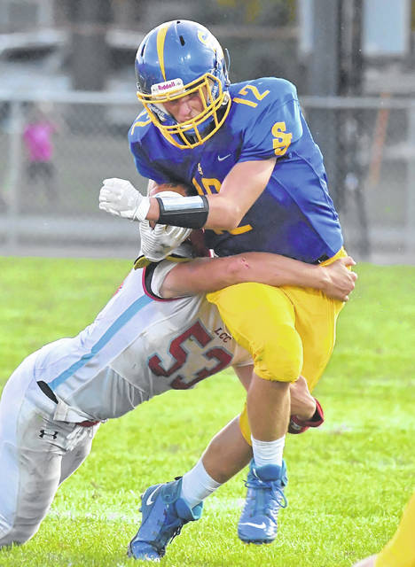 Jordan Brown of Delphos St. John's fights for yardage against Lima Central Catholic's Caleb Heider during Saturday's night's game at Stadium Park in Delphos.