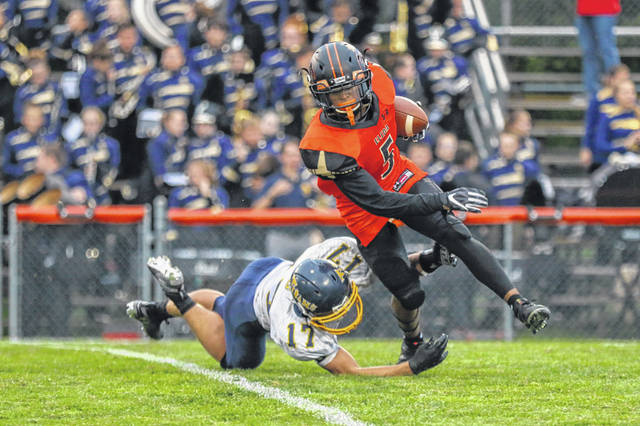 Elida's Marcel Poe tries to get away from Ottawa-Glandorf's Jarrod Beach during Friday night's game at Elida.