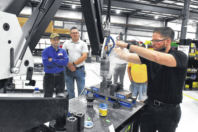Tyler Albert, an employee for FlexArm I FlexCNC in Wapakoneta, demonstrates a FlexArm GHM-45 tapping arm during Thursday's open house for Kris Rhamy, left, and Jason Corn of Bulldog Battery in Wabash, Indiana.