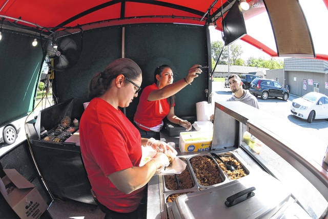 Letzly Arellano, center, points out the menu to a customer as Dulce Montenegro, left, prepares a meal working inside Taco Movil food truck.