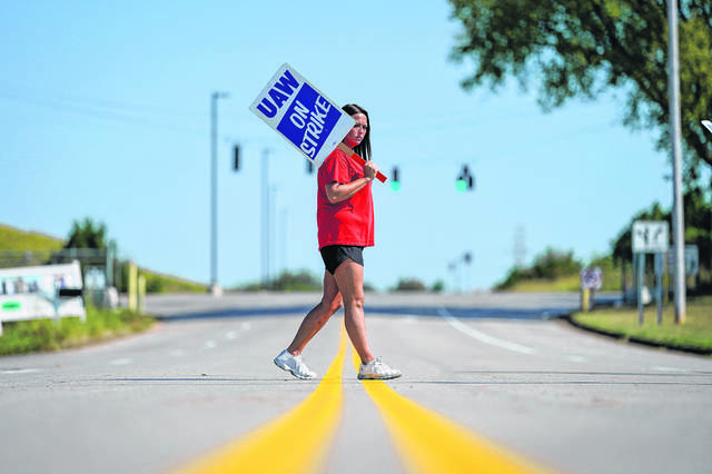 Temporary plant worker Shanuel Merevith, of Edmonson County, Ky., carries a sign and walks the picket line outside the as General Motors assembly plant in Bowling Green, Ky, Monday, Sept. 16, 2019. Thousands of members of the United Auto Workers walked off General Motors factory floors or set up picket lines early Monday as contract talks with the company deteriorated into a strike.