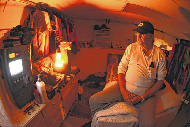 "Lit by a lava lamp, John Stemen, a resident with Restoration House of Lima on South Collett Street, sits on the edge of his bed in the basement. ""It's got its good days and some bad days. We all get along with each other, and it's a good place,"" Stemen said."