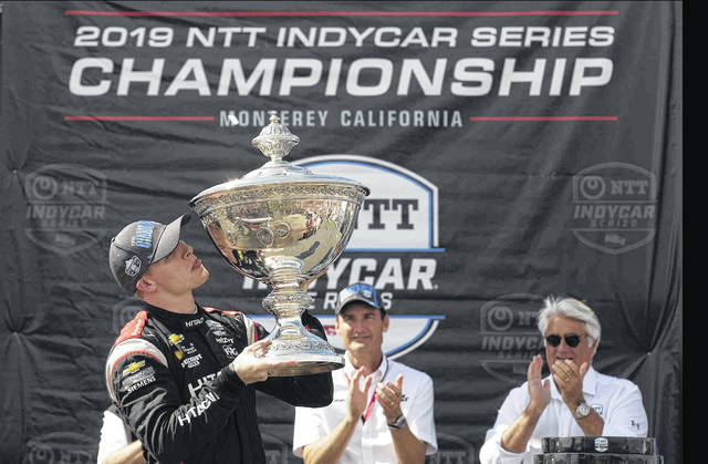 Josef Newgarden, left, kisses the trophy after winning the championship after an IndyCar auto race at Laguna Seca Raceway in Monterey, Calif., Sunday, Sept. 22, 2019. (AP Photo/David Royal)