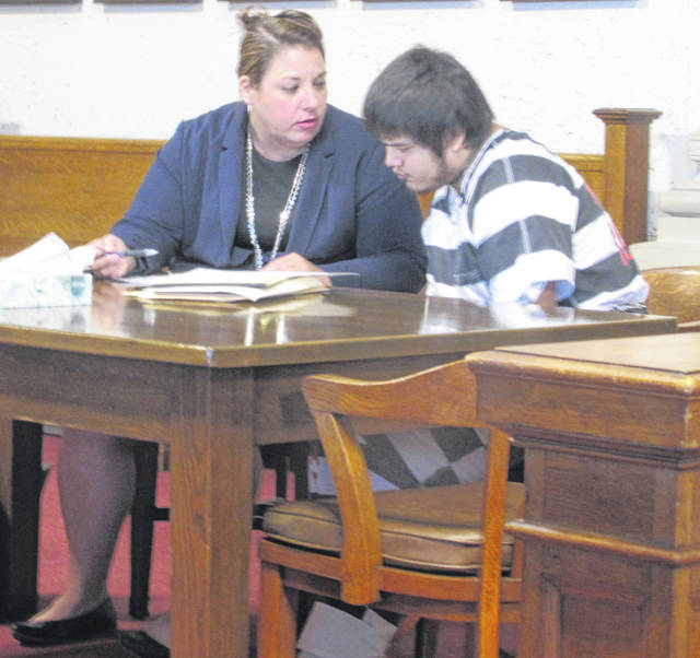 Attorney Elizabeth Smith speaks to her client Leipsic resident Isaiah Oliver, who pleaded guilty to aggravated robbery during a final pre-trial hearing Thursday in Putnam County.