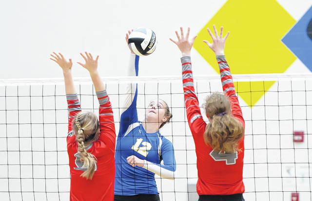 Miller City's Sofie Van Wezel spikes against Columbus Grove's Megan Blankemeyer, left, and Cassie Heilman during Wednesday's volleyball match at Miller City High School.