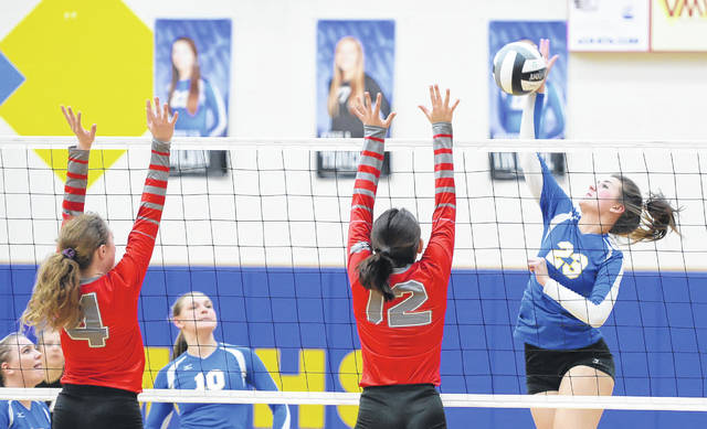 Miller City's Katelyn Kuhlman spikes against Columbus Grove's Cassie Heilman, and Becca Choi during Wednesday's volleyball match at Miller City High School.