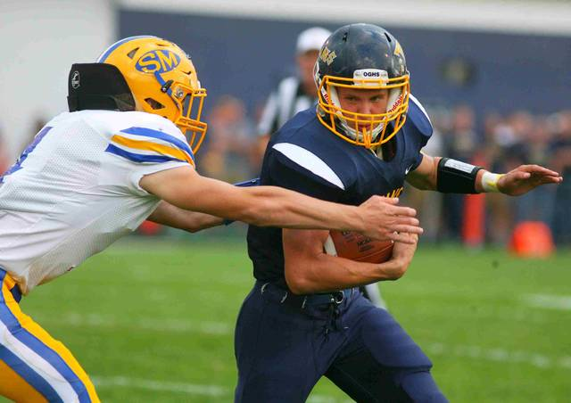 Ottawa-Glandorf's Clayton Recker looks to shake St. Marys' Lukas Walters during Friday night's game at Ottawa-Glandorf.