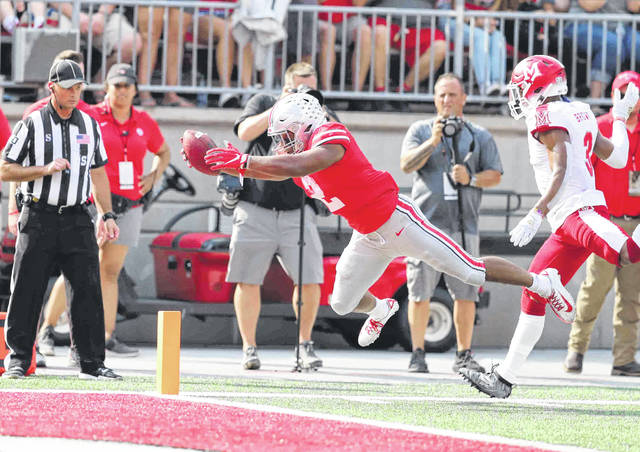 Ohio State's J.K. Dobbins dives into the end zone for a touchdown ahead of Miami of Ohio's Mike Brown during Saturday's game against Miami of Ohio at Ohio Stadium in Columbus.