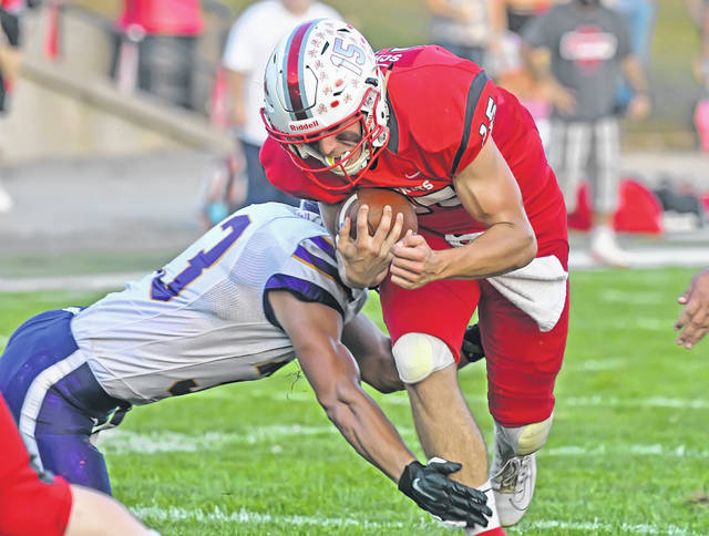Pandora-Gilboa's Silas Schmenk fights for yardage against Leipsic's Cole Williamson during Friday night's game at Pandora Park.