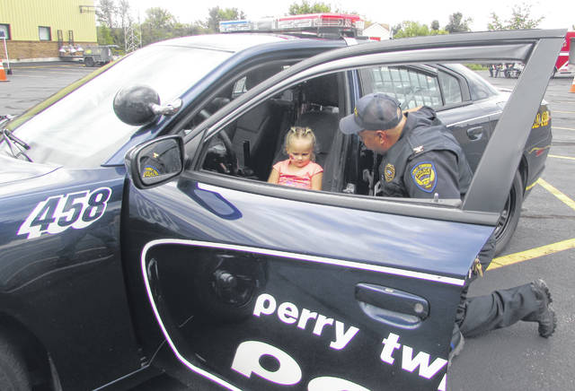 Harper Clabaugh, 2 1/2, of Lima, gets to sit inside a police car, assisted by Perry Township Police Chief Bob Phillips.